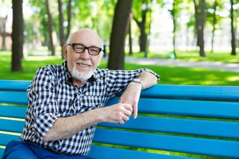 Happy man on bench after selling his life insurance