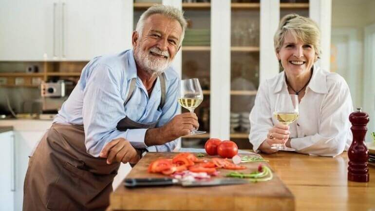 A smiling couple in the kitchen happy to avoid life insurance lapsation