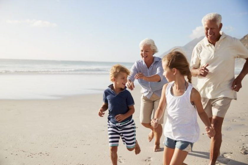 Grandparents Running Along Beach With Grandchildren On Summer Vacation.