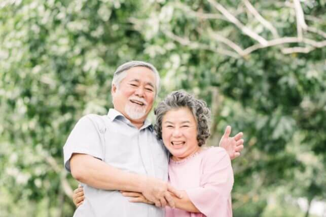 Happy Asian senior couple having a good time in the park.