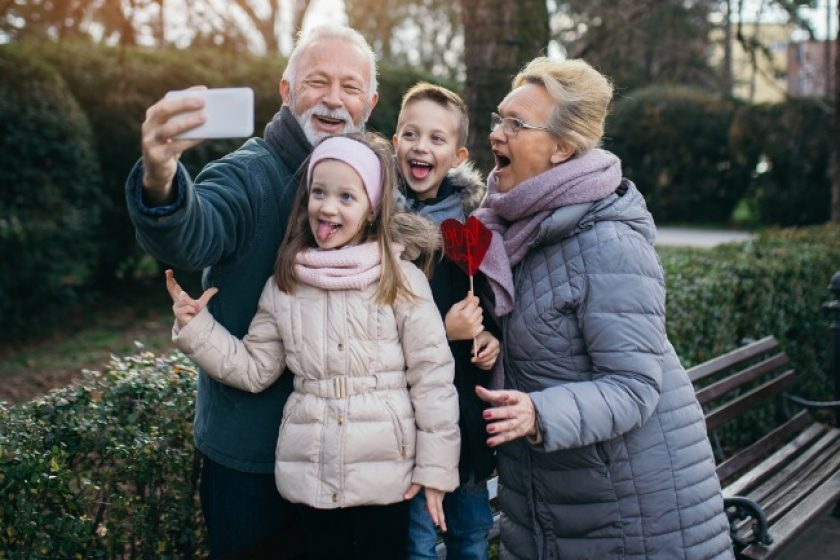 Grandparents taking selfie photo with their grandchildren in city park after discussing can you have multiple life insurance policies.