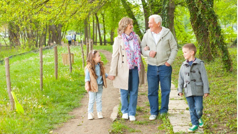 Grandparents with grandchildren in park discussing retained death benefits.