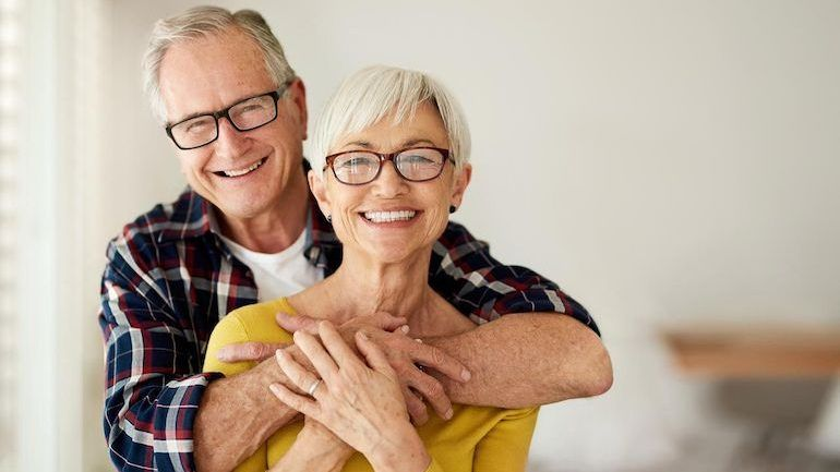 Senior man embracing his wife discussing selling their whole life insurance policy.
