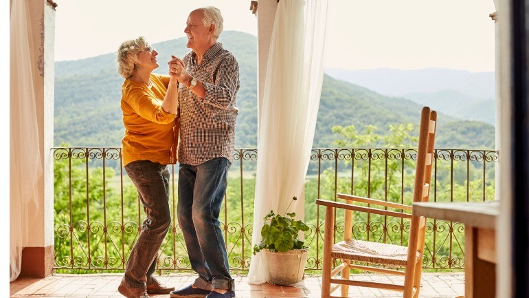 Senior couple dancing and discussing term vs. whole life insurance policies.