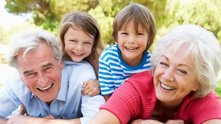 Couple playing outside with grandchildren after discovering the the difference between term and whole life insurance.