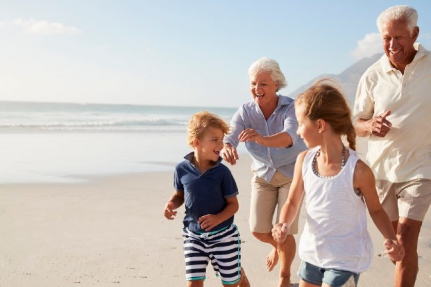 Grandparents Running Along Beach With Grandchildren discussing what a beneficiary is.