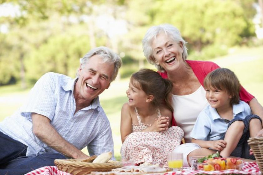 Grandparents And Grandchildren Enjoying Picnic Together Laughing.