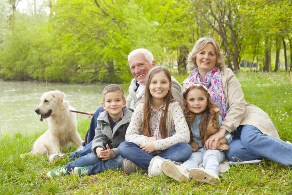 Grandparents, grandchildren and their dog sitting on the ground in park.