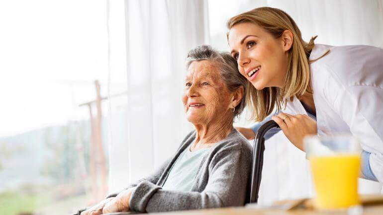 An elderly parent with her long-term care assistant
