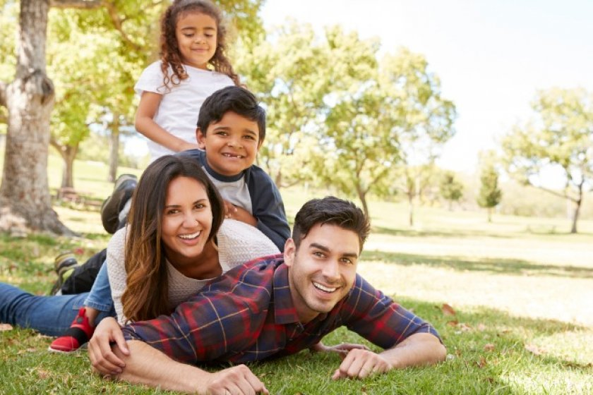 Family playing together in park after decreasing term life insurance