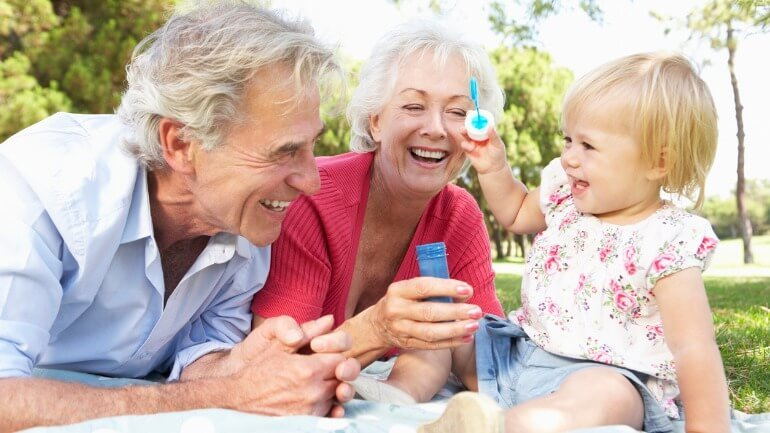 Grandparents playing in park with granddaughter after checking on their social security benefits.