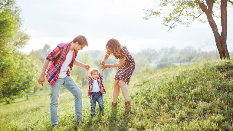 Parents and child in a grassy field who received a life insurance payout.