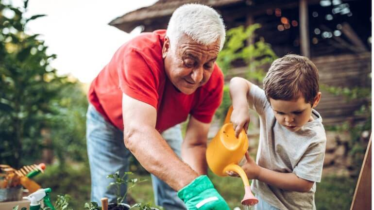 Grandfather and grandson in the garden thinking about having too much life insurance.