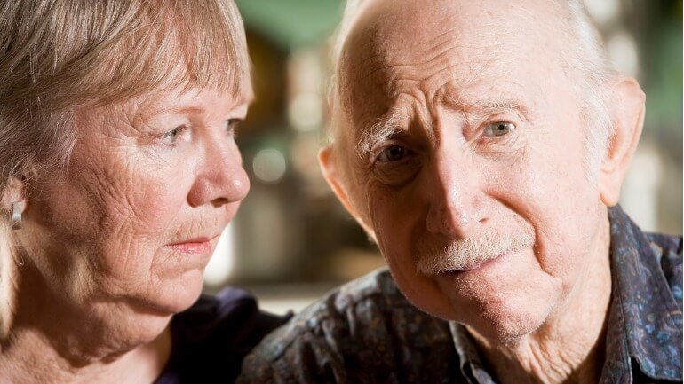 Elderly couple looking worried.