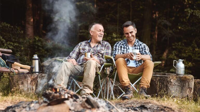 A father and son camping after getting the best deal on a senior life settlement.