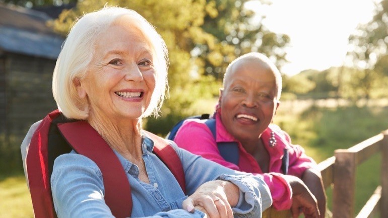 Portrait Of Two Female Senior Friends Hiking In Countryside.
