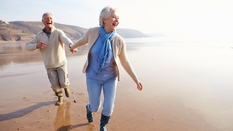 Senior couple enjoying the beach saying long term care insurance is worth it.