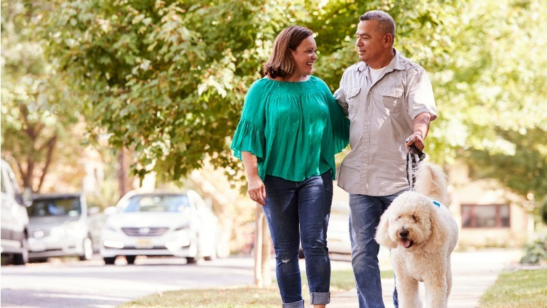 A couple walking their dog after surrendering their life insurance policies.