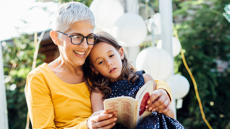 A long-term care insurance beneficiary reading a book to her grand child
