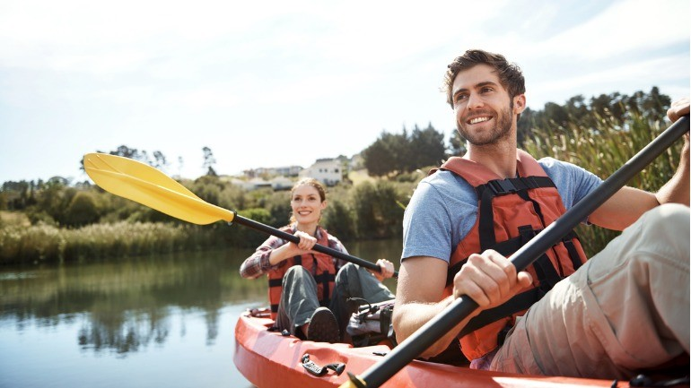 Two people in a kayak talking about the tax consequences of surrendering life insurance policies.