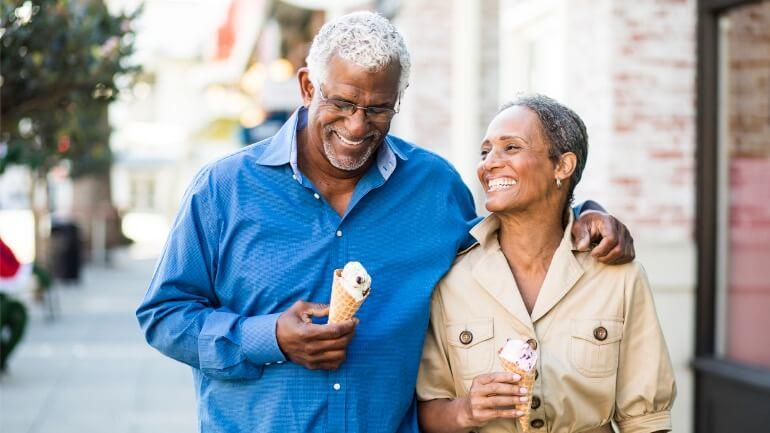 Couple walking eating ice cream while using life insurance for retirement income.