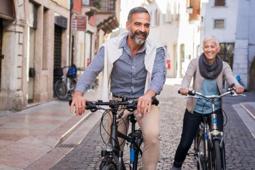 Elderly couple riding bikes exploring long term care insurance pros and cons.