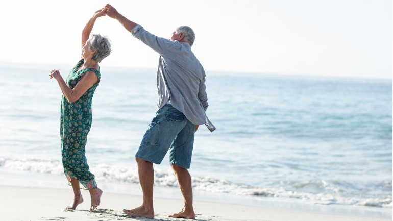 Senior couple dancing on the beach after buying long term care insurance.