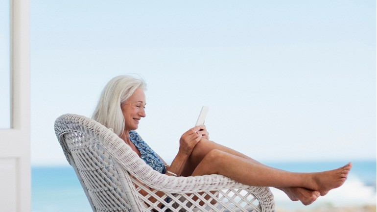 Senior woman reading the best retirement blogs on her tablet at the beach.
